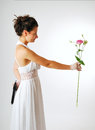 Pretty bride with a flower and a gun is reaching out gentle hiding black handgun behind back white low necked dress accentuates Stock Photography