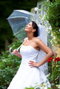 Pretty bride her wedding day raining day nice flowers around nice transparent umbrella Stock Image