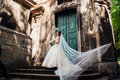 Pretty bride looks over her shoulder while wind blows her veil Royalty Free Stock Photo