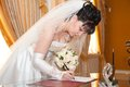Pretty bride signing document beautiful marriage license or wedding contract Royalty Free Stock Photography