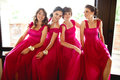 Pretty bridesmaids in pink dresses sit behind a big window Royalty Free Stock Photo