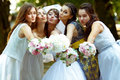 Pretty bridesmaids surround a bride holding wedding bouquets in Royalty Free Stock Photo