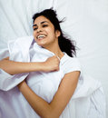 Pretty brunette in bed smiling having fun Stock Photo