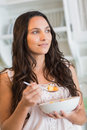 Pretty brunette eating a fruits salad in the kitchen Stock Photo