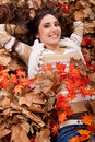 Pretty brunette  girl in dry autumn leaves Royalty Free Stock Photo