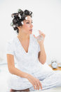 Pretty brunette in hair rollers drinking glass of water at home bedroom Royalty Free Stock Photos