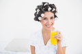 Pretty brunette in hair rollers holding glass of orange juice sm smiling at camera at home bedroom Royalty Free Stock Photos