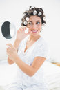 Pretty brunette in hair rollers looking in hand mirror and using eyelash curler bedroom at home Royalty Free Stock Image