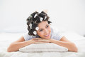 Pretty brunette in hair rollers lying on her bed bedroom at home Stock Image