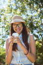 Pretty brunette having coffee to go on a summers day Stock Photos