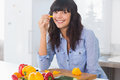 Pretty brunette holding slice of pepper at kitchen counter Royalty Free Stock Image