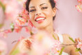 Pretty brunette lady among the flowers pink Royalty Free Stock Images