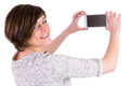 Pretty brunette looking at camera and taking a picture with her smartphone Royalty Free Stock Photo