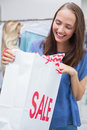 Pretty brunette opening a discounted bag Royalty Free Stock Photo