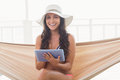 Pretty brunette relaxing on a hammock and using tablet pc Royalty Free Stock Photo