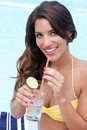 Pretty brunette sipping drink near pool Royalty Free Stock Photo