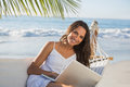 Pretty brunette sitting on hammock with laptop smiling at camera the beach Royalty Free Stock Photos