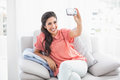 Pretty brunette sitting on her sofa taking a picture of herself Royalty Free Stock Photo