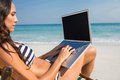 Pretty brunette using laptop on deck chair Royalty Free Stock Photo