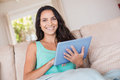 Pretty brunette using tablet pc on the couch Royalty Free Stock Photo