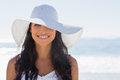 Pretty brunette in white sunhat smiling at camera on the beach Royalty Free Stock Photos