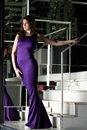 Pretty brunette woman in long purple dress Stock Photos