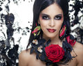 Pretty brunette woman with rose jewelry, black and red, bright make up kike a vampire closeup red lips Royalty Free Stock Photo