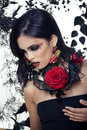Pretty brunette woman with rose jewelry black and red close up Stock Photo