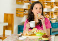 Pretty brunette woman sitting at table inside bakery, holding cup of coffee and biting into bread slice Royalty Free Stock Photo