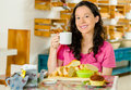 Pretty brunette woman sitting at table inside bakery, holding cup of coffee and smiling happily, bread selection in Royalty Free Stock Photo