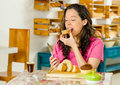 Pretty brunette woman wearing pink shirt sitting at table inside bakery, biting into slice of bread Royalty Free Stock Photo