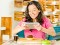 Pretty brunette woman wearing pink shirt sitting by table inside bakery, using mobile phone to take photo of bread slice Royalty Free Stock Photo