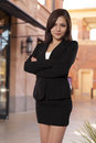 Pretty business woman stands with her arms crossed confident in a skirt and vest Stock Images