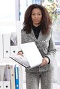 Pretty businesswoman with folder young afro american holding standing in bright office Stock Image