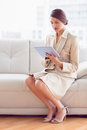 Pretty businesswoman sitting on sofa using tablet pc in the office Stock Photography