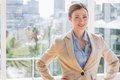Pretty businesswoman smiling at camera with hands on hips by large windows Royalty Free Stock Photo