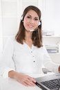 Pretty businesswoman in white sitting at helpdesk and laptop wit Royalty Free Stock Photo