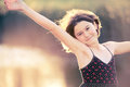 Pretty carefree girl backlit half body shot of happy smiling and raising her arms up in a pose Stock Photography