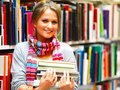 Pretty charming lady holding books in library Stock Image