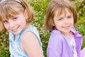 Pretty children and teenager girls on green grass Stock Photos