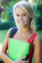 Pretty college student outdoors smiling blonde with files in hand standing Stock Photos