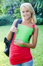 Pretty college student outdoors smiling blonde with files in hand standing Royalty Free Stock Photo