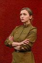 Pretty concentrated girl in Soviet World war II uniform at red w Royalty Free Stock Photo