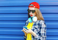 Pretty cool girl listens to music in headphones and using smartphone over blue background Royalty Free Stock Photo