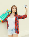 Pretty cool girl with skateboard taking picture self portrait on smartphone over white Royalty Free Stock Photo