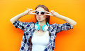 Pretty cool girl in sunglasses and headphones having fun