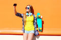 Pretty cool smiling girl in sunglasses with skateboard taking picture self portrait on smartphone Royalty Free Stock Photo