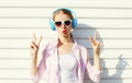 Pretty cool woman listens to music in headphones over white background Royalty Free Stock Image
