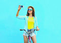 Pretty cool young woman taking self portrait on smartphone with retro bicycle over colorful blue