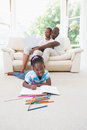 Pretty couple using laptop on couch and their daughter drawing Royalty Free Stock Photo